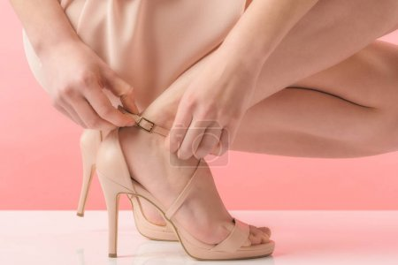 partial view of girl in pink heels, on pink