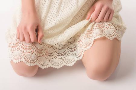 Photo pour Vue partielle d'une fille passionnée en robe de dentelle blanche, isolé sur blanc - image libre de droit