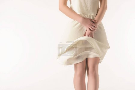 cropped view of elegant girl in waving white dress, isolated on white