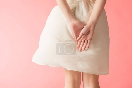 midsection view of woman posing in elegant white dress, isolated on pink