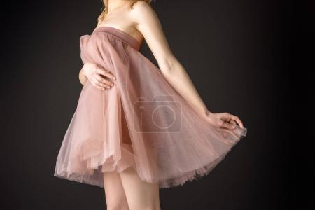 midsection view of tender girl posing in pink chiffon dress, isolated on grey