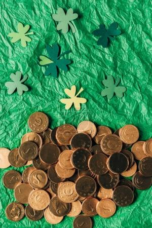 top view of golden coins and paper shamrock on green surface, st patricks day concept