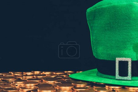 green hat on golden coins isolated on black, st patricks day concept