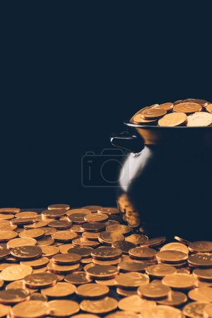 black pot with shining golden coins isolated on black, st patricks day concept