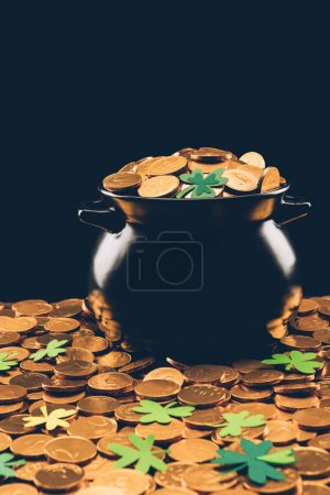black pot with golden coins isolated on black, st patricks day concept
