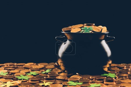 black pot with golden coins and shamrock isolated on black, st patricks day concept