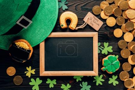 top view of empty board with gingerbread and shamrock on table, st patricks day concept
