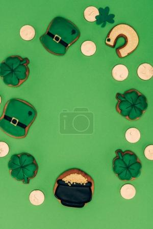 top view of icing cookies and golden coins isolated on green, st patricks day concept