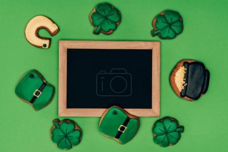 Photo for Top view of empty board with icing cookies isolated on green, st patricks day concept - Royalty Free Image