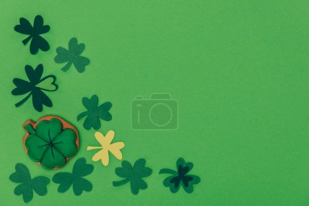 top view of gingerbread in shape of shamrock and paper shamrock isolated on green, st patricks day concept