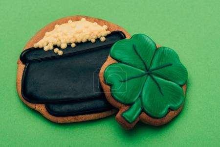 high angle view of icing cookies in shape of pot with coins and shamrock on green, st patricks day concept