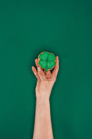 cropped image of woman holding cookie in shape of shamrock isolated on green, st patricks day concept