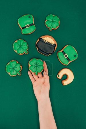 cropped image of woman holding icing cookies isolated on green, st patricks day concept