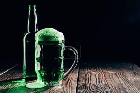 Photo pour Verre et bouteille de bière verte sur table en bois, concept de jour st patricks - image libre de droit