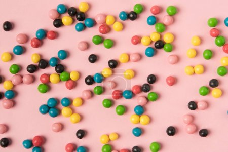 close up view of various candies isolated on pink