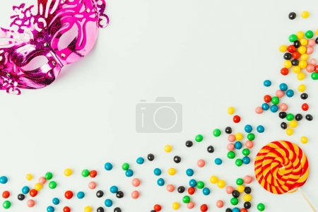 flat lay with arranged masquerade mask, lollipop and sweets isolated on white