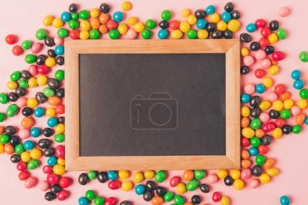 top view of candies and empty blackboard isolated on pink
