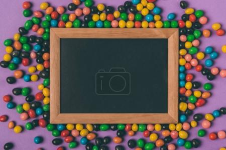 top view of candies and empty blackboard isolated on purple