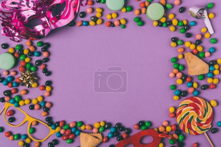 top view of arranged masquerade masks, candies and cookies isolated on purple