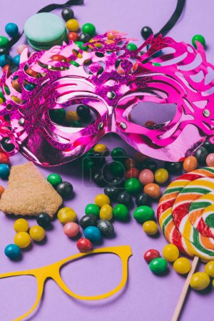 close up view of masquerade masks and candies isolated on purple
