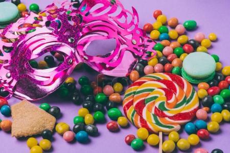 Photo pour Vue rapprochée du masque de mascarade, sucette et bonbons isolés sur violet - image libre de droit