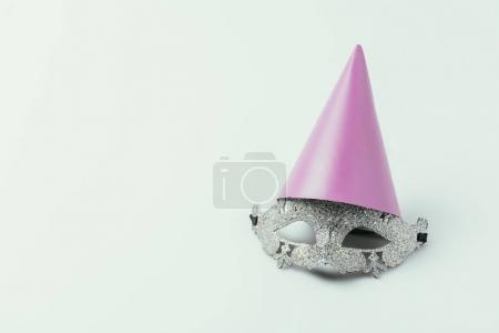 close up view of masquerade mask and party cone isolated on grey