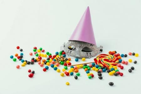 close up view of masquerade mask, party cone and sweets isolated on grey