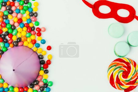 top view of arranged party cone, masquerade mask, macarons and candies isolated on grey