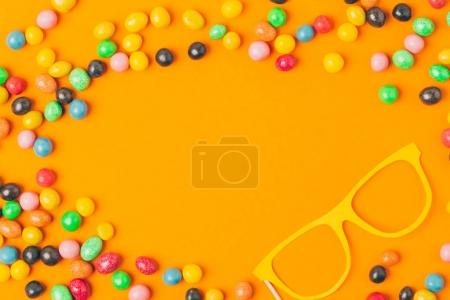 top view of party mask and sweets isolated on orange, purim holiday concept