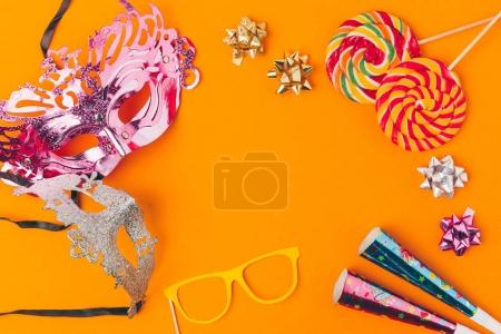 flat lay with lollipops and party objects isolated on orange, purim holiday concept