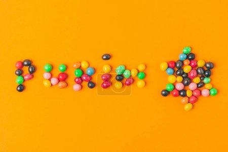vue de dessus du lettrage de Pourim fait de bonbons et étoiles isolées sur orange