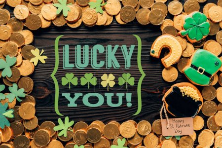 flat lay with golden coins, festive cookies and lucky you lettering on wooden surface