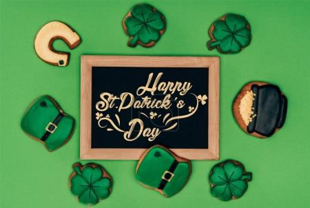 top view of festive cookies and blackboard with happy st patricks day lettering isolated on green