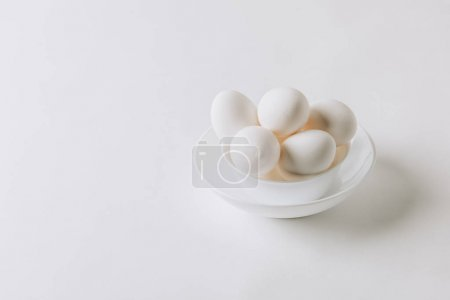 Photo for White eggs laying on white plate on white background - Royalty Free Image
