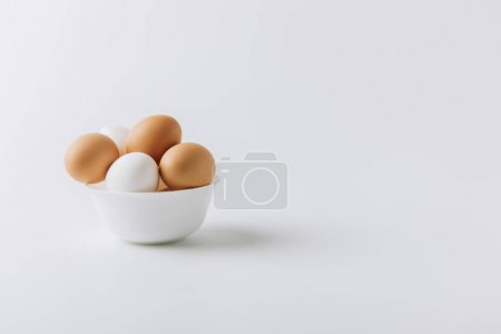 Photo for White and brown eggs laying on white plate on white background - Royalty Free Image