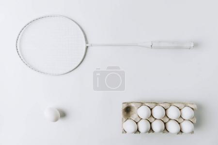 white egg on white background with another white eggs in carton and racket
