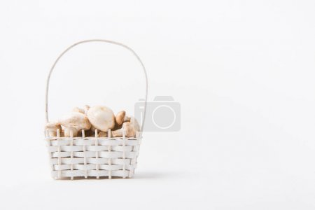 heap of champignon mushrooms laying in wicker basket on white background