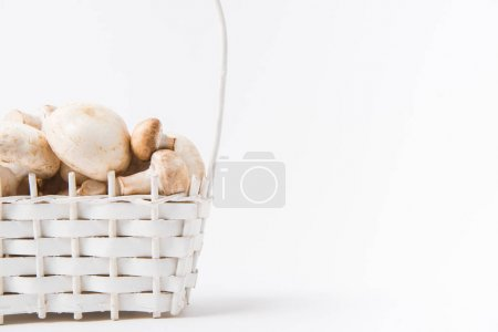 heap of mushrooms laying in wicker basket on white background