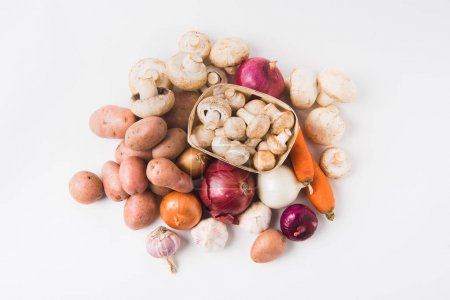 Photo for Heap of mushrooms laying in basket over vegetables on white background - Royalty Free Image