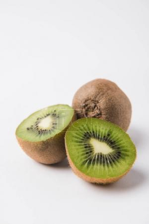 whole and halved kiwi laying on white background