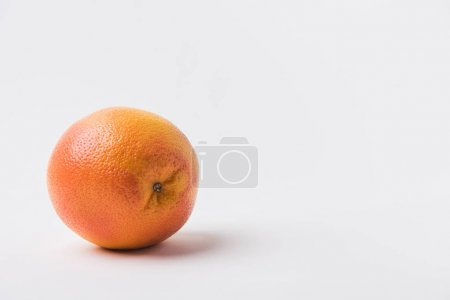 raw unpeeled orange laying on white background