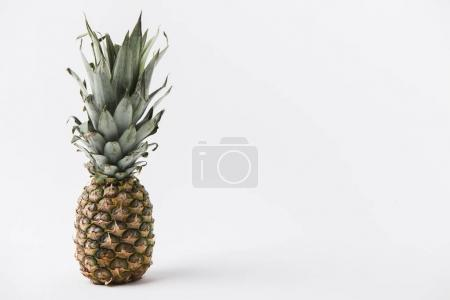 raw unpeeled pineapple laying on white background
