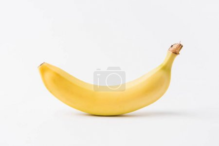 raw unpeeled banana laying on white background