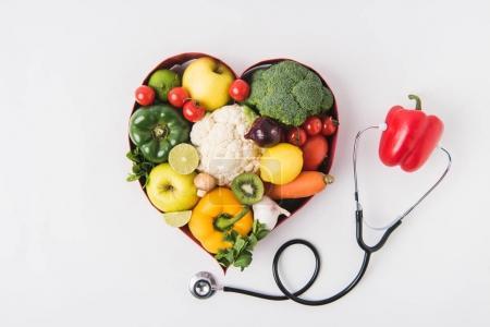 Photo pour Légumes et fruits dans un plat en forme de coeur près du poivre avec stéthoscope isolé sur fond blanc - image libre de droit