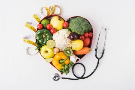 Photo for Vegetables and fruits laying in heart shaped dish near stethoscope and measuring tape isolated on white background - Royalty Free Image