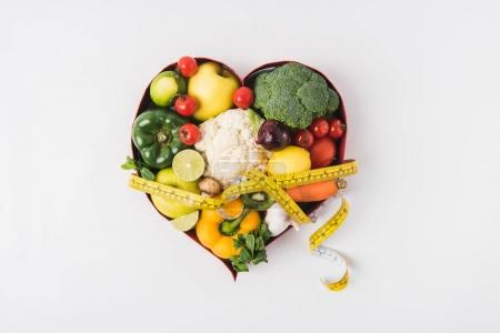 vegetables and fruits laying in heart shaped dish near stethoscope and measuring tape isolated on white background