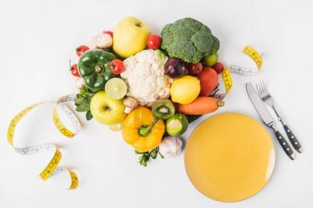 Photo for Vegetables and fruits laying on white background with fork, spoon, measuring tape and plate - Royalty Free Image