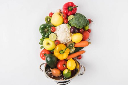 Eating healthy concept with vegetables and fruits in colander isolated on white background