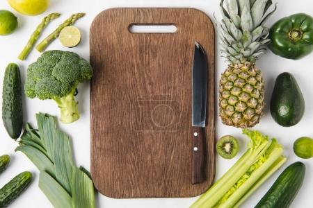 Knife on wooden cutting board with green vegetables and fruits isolated on white background
