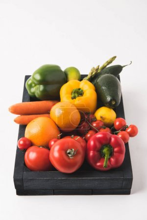 Raw colorful vegetables and fruits in dark wooden box isolated on white background